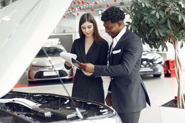 Salespeople reviewing documentation at a car dealership