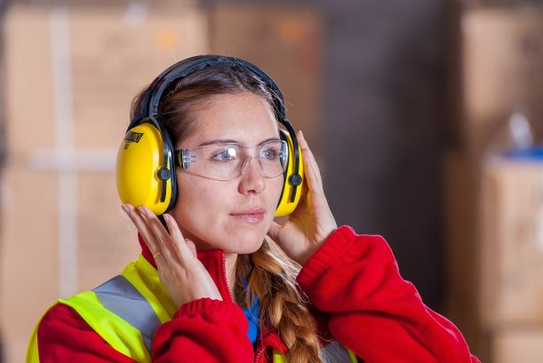 Female industrial worker wearing safety glasses and hearing protection