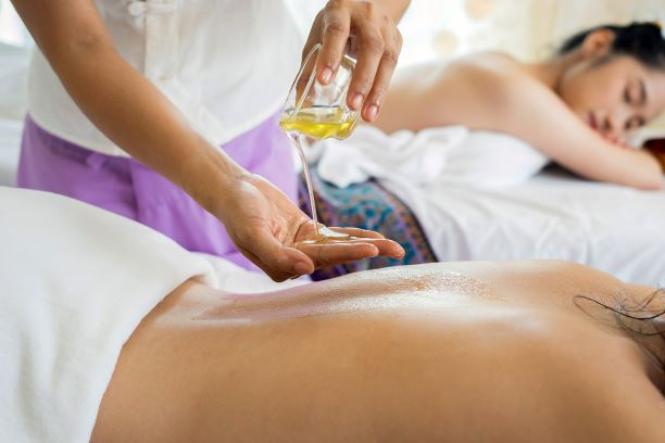Applying massage oil to the back of a woman in a spa