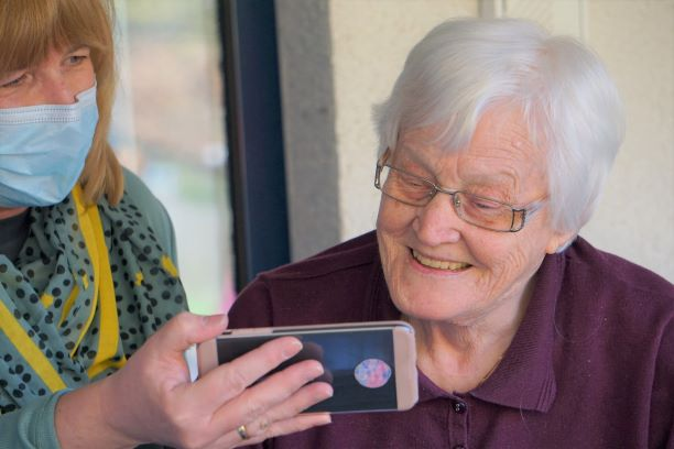 Retirement age woman watching an iPhone that a younger lady wearing a mask is holding for her