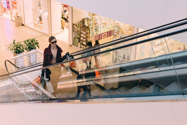 Woman walking up escalator in a shopping mall